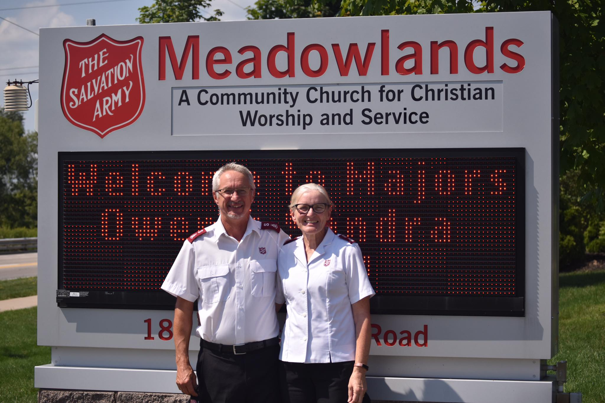 Majors Owen and Sandra Budden in front of corps sign